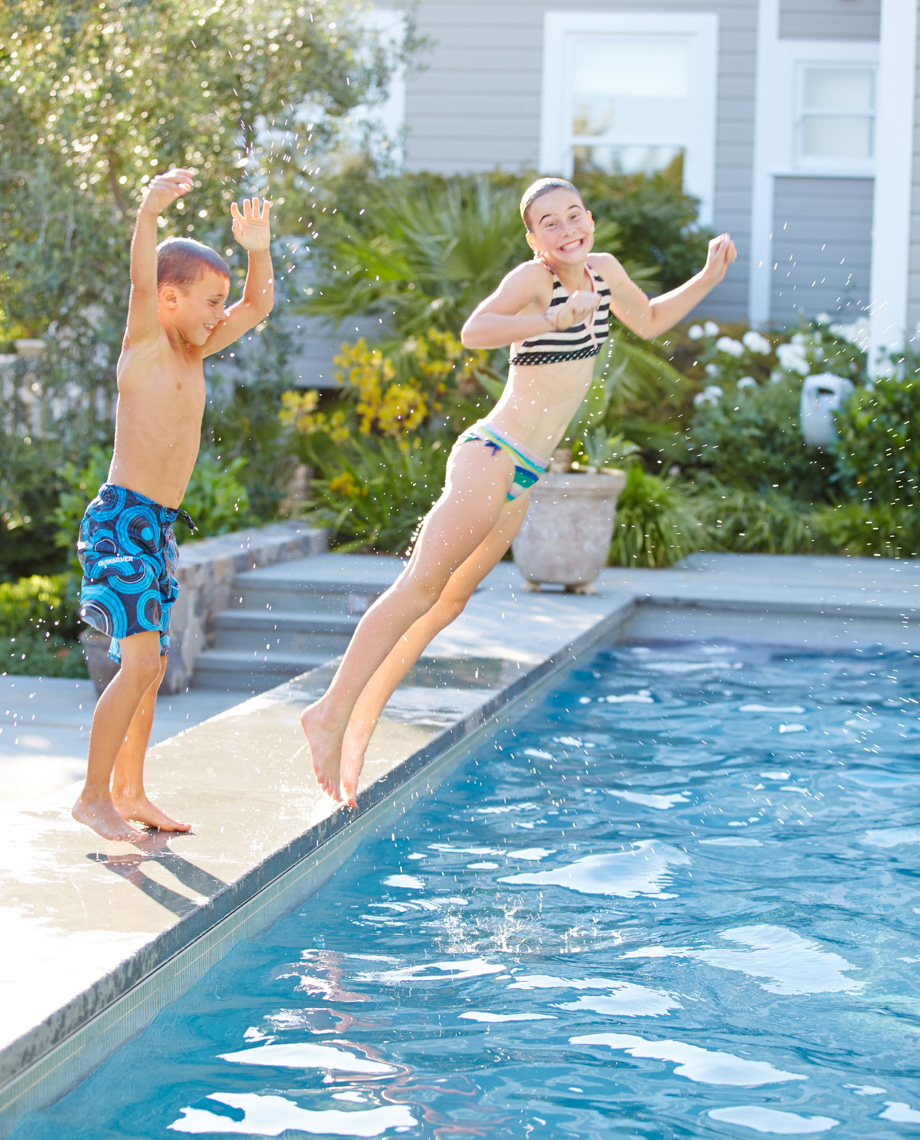 Girl in bathing suit is falling into outdoor pool in the son while younger brother jumps from the edge of the pool
