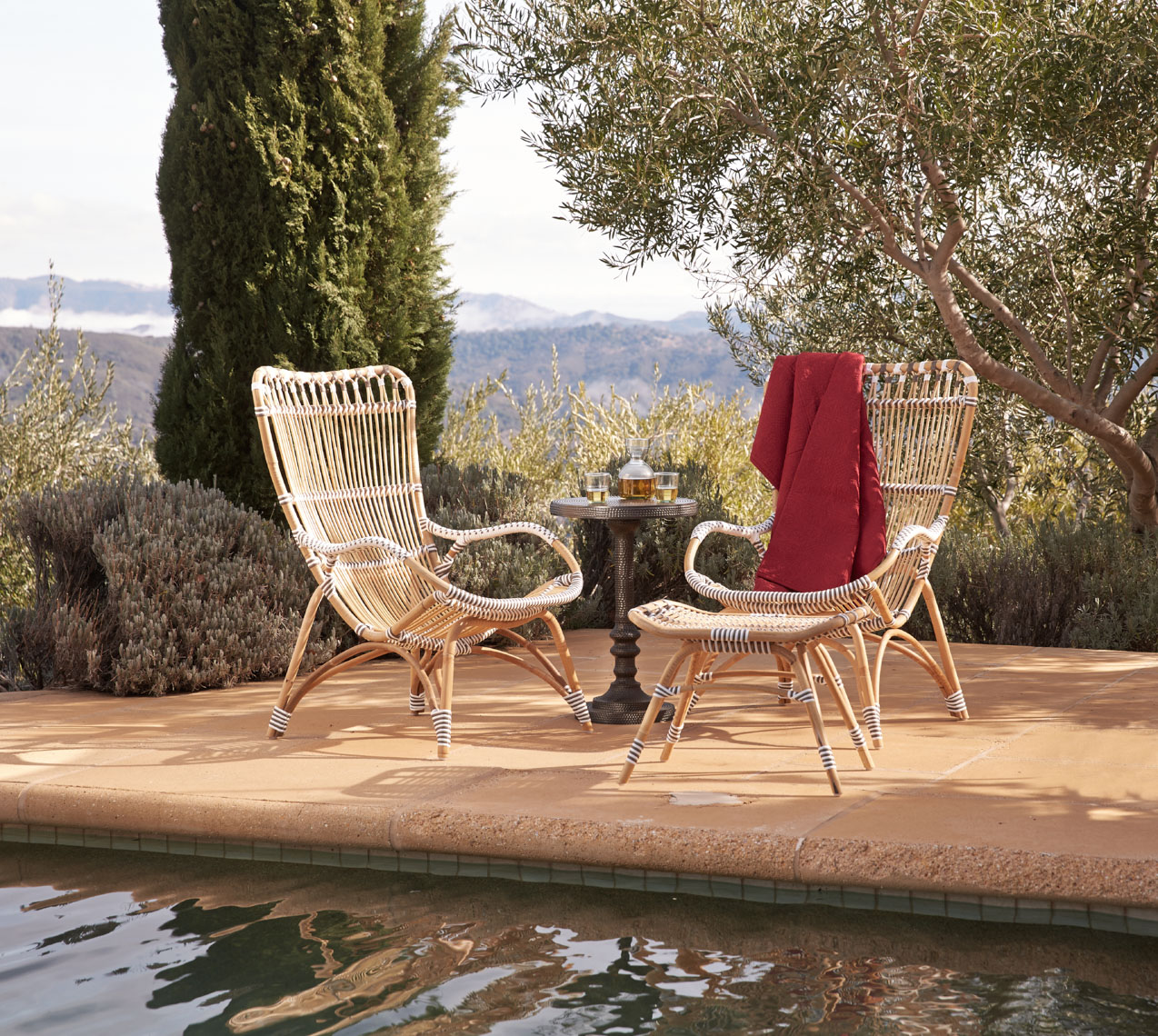 Two bamboo chairs on tile patio near pool in Napa