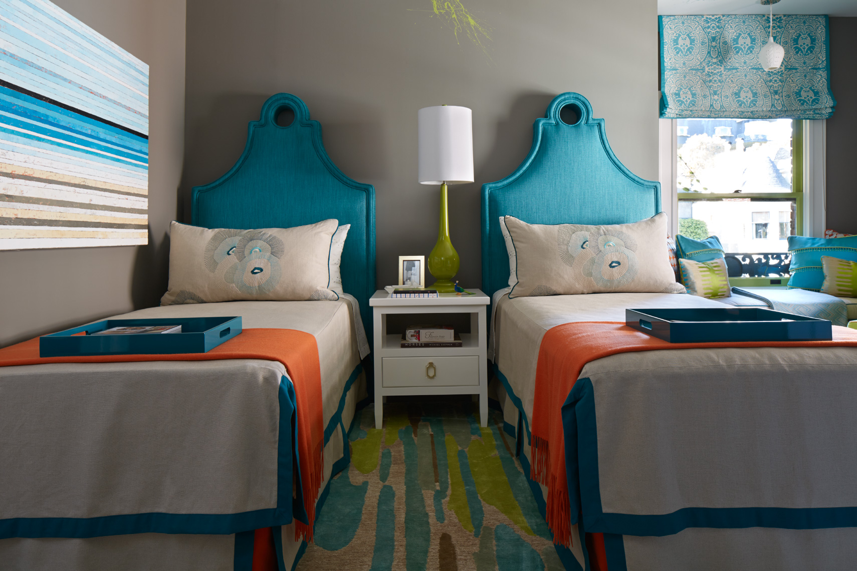 set of twin beds with blue headboards and bedding with orange blankets