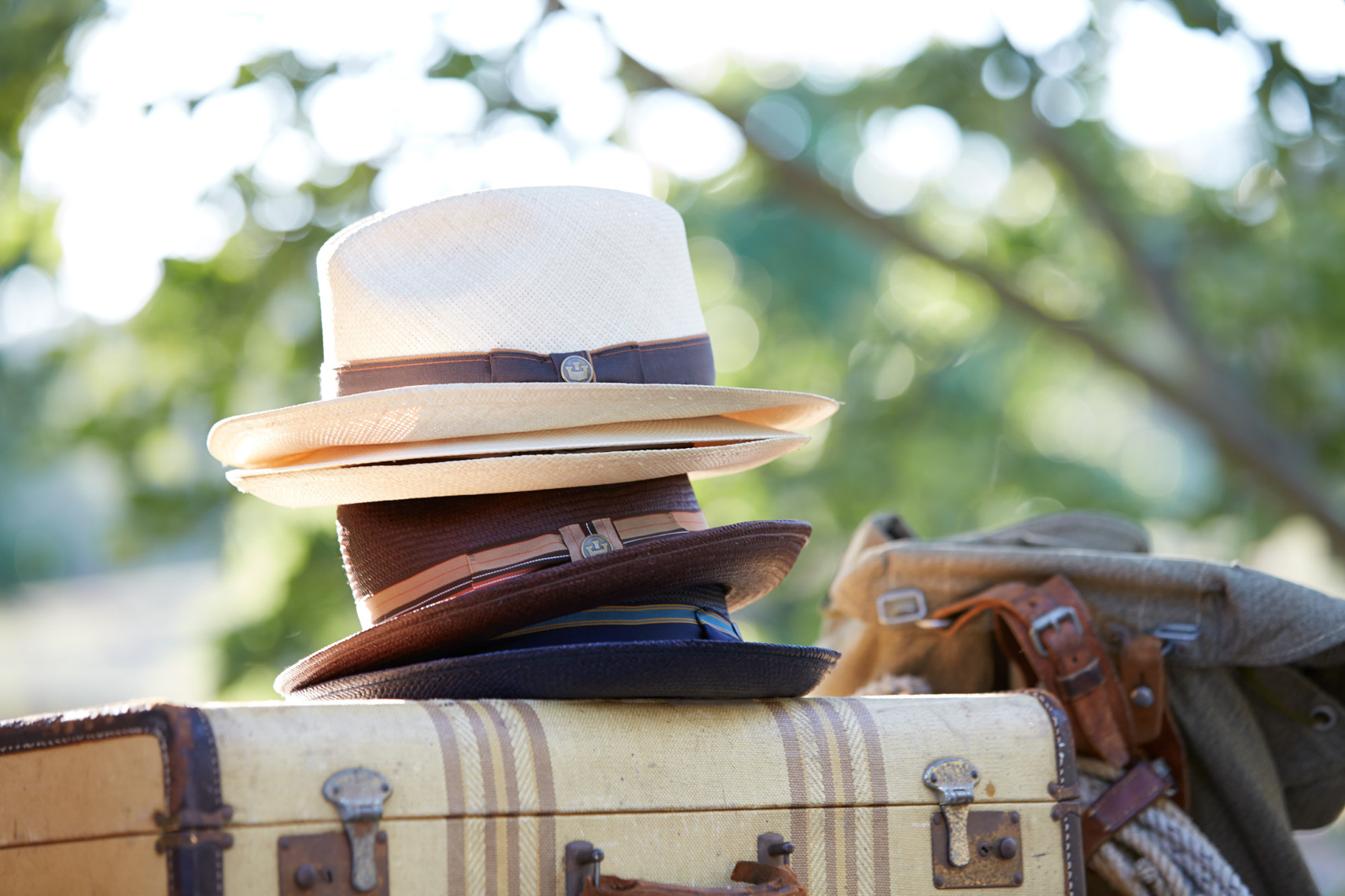 stack of white and brown hats on tan suitcase with backpack