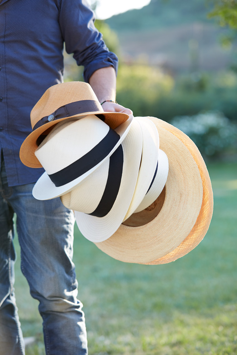 man holding stack of white and tan sun hats San Francisco product photographer