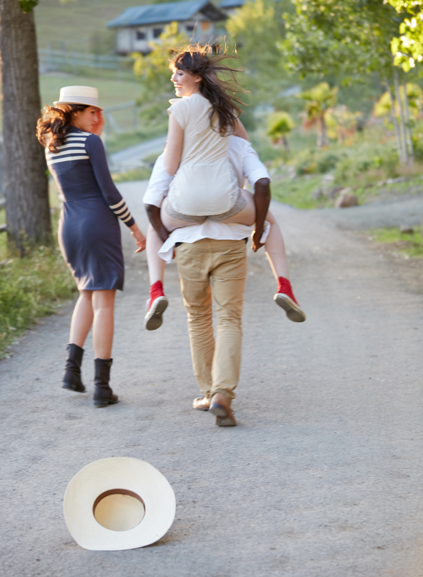 Two women and a man walk down a road with the woman ridding on the man
