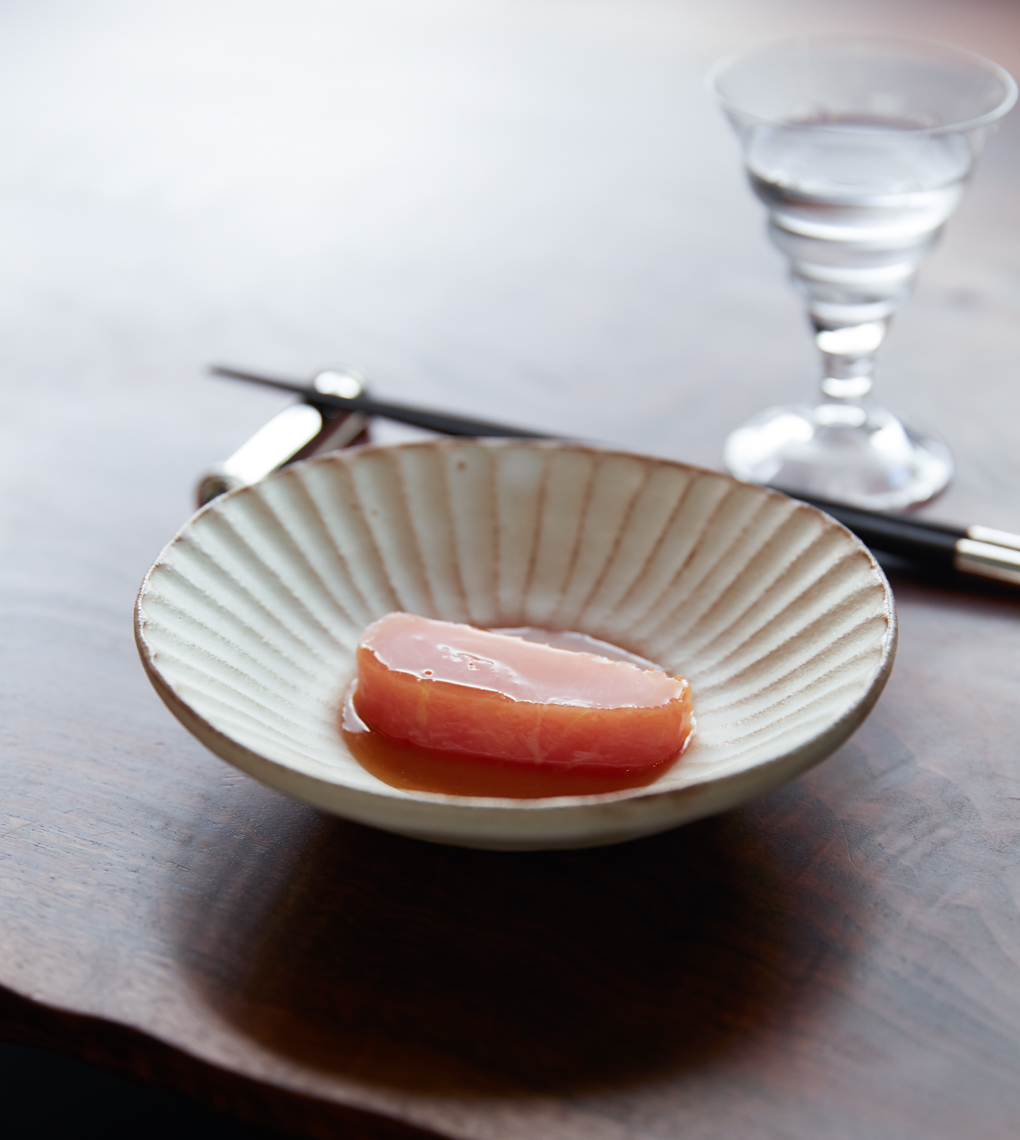 slice of salmon with sauce in white shell bowl on wooden table