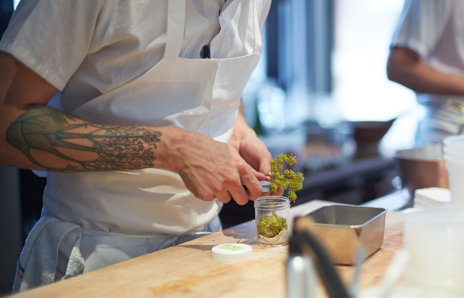 Chef slicing food at prep table in restaurant kitchen