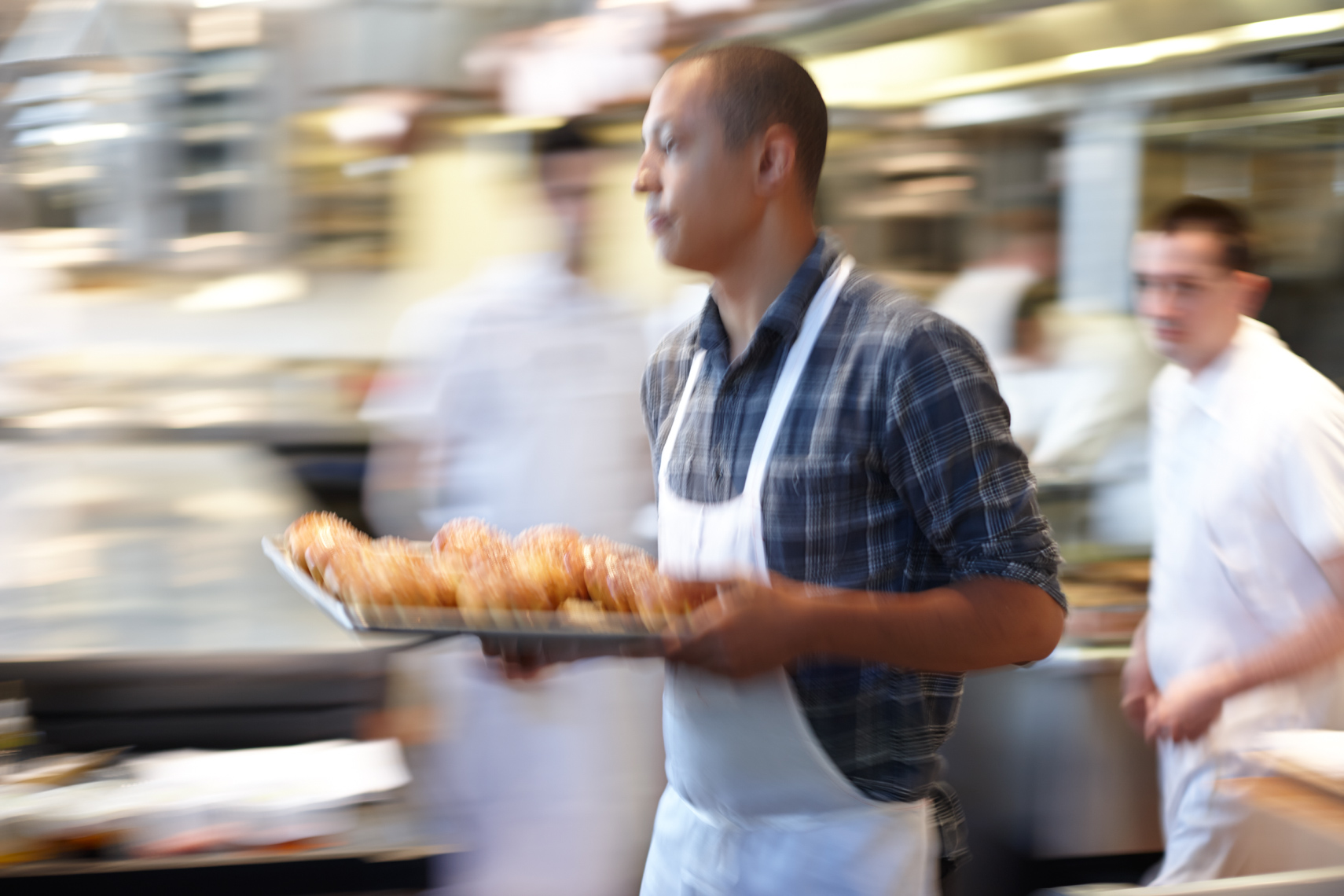 Waiter in white apron rushing through kitchen with a tray of food