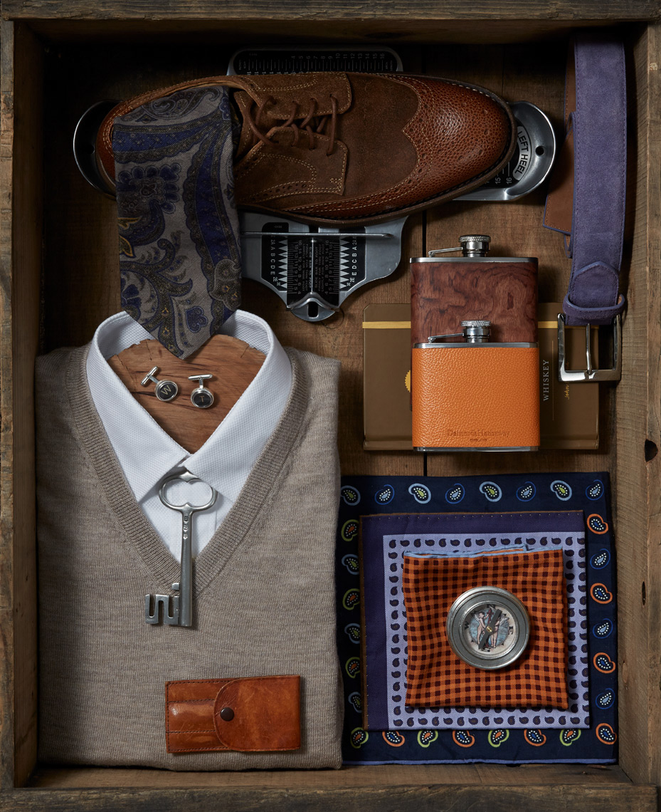 old wooden box with brown shoe and white folded shirt with grey vest and flasks San Francisco product photographer