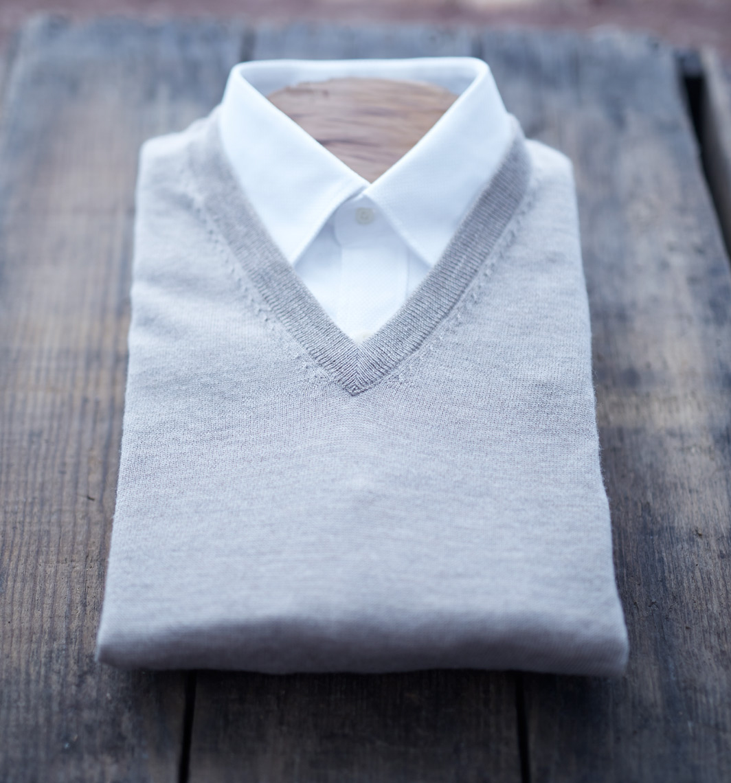 folded white shirt with grey vest on outdoor wooden table