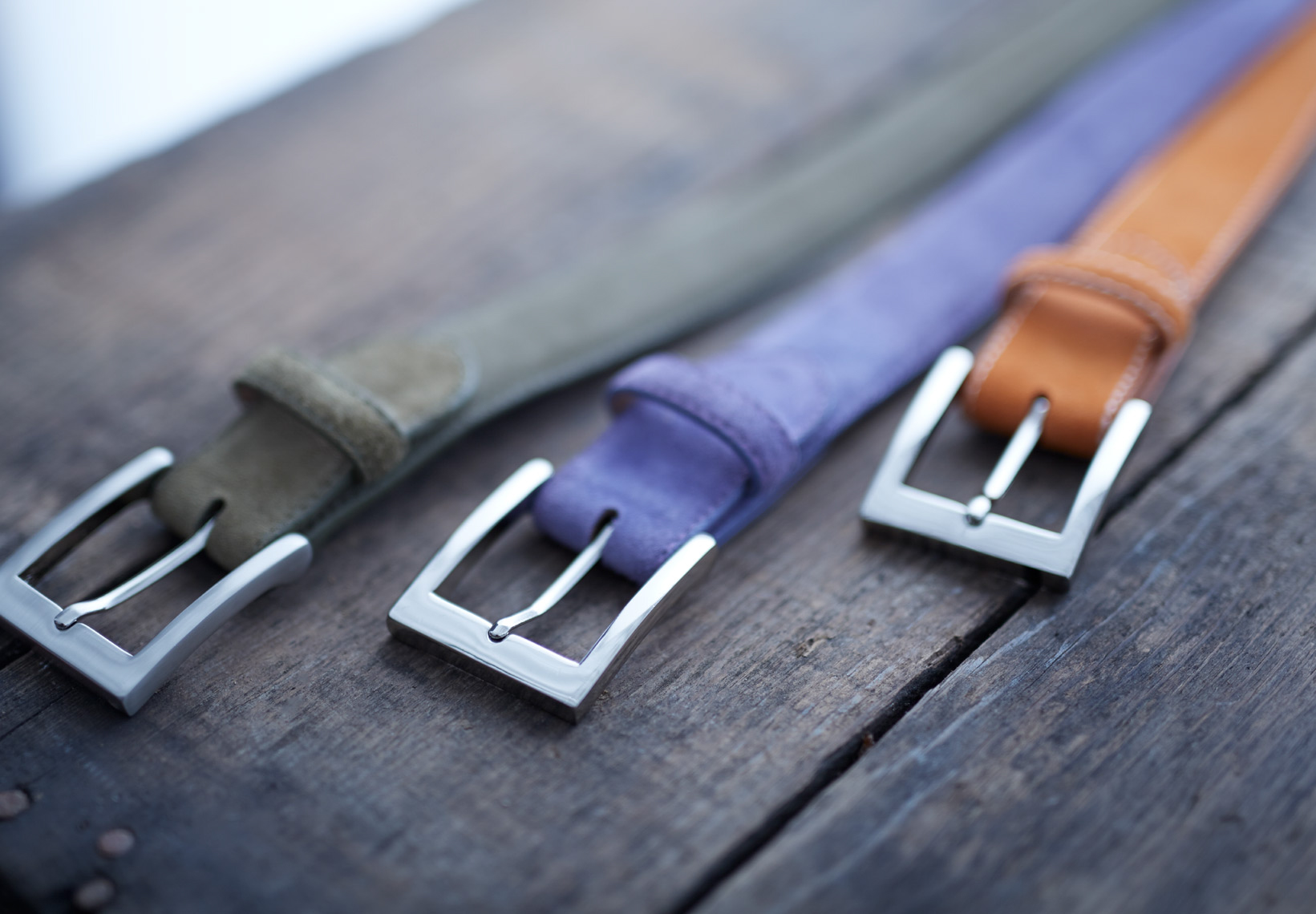 3 green and purple and orange belts on outside wooden picnic table