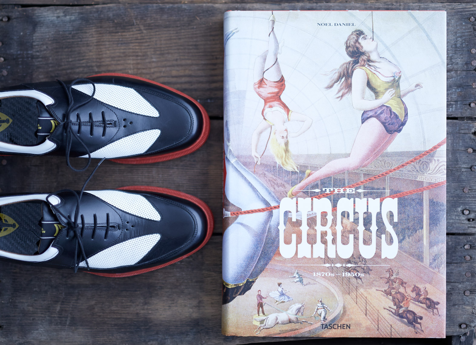 black and white saddle shoes with red soles next to circus book