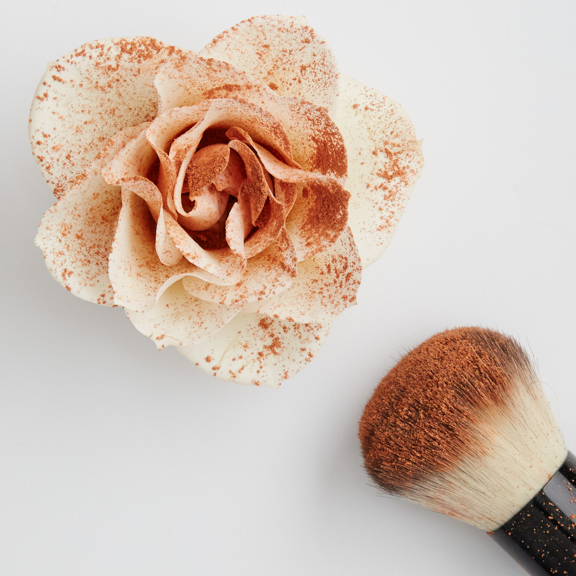 blush brush with powder sprinkled on white rose