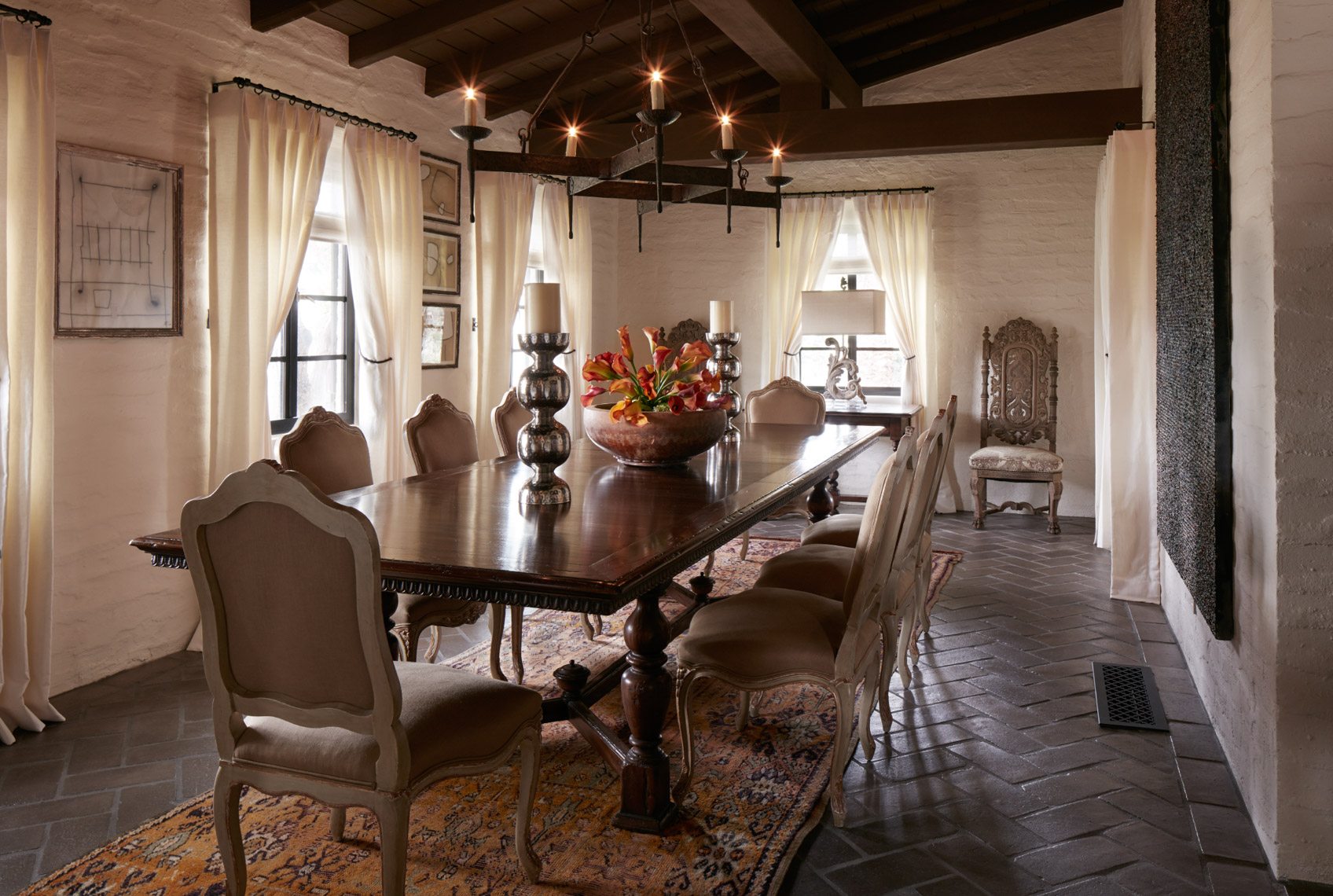 wooden dining room table with beige chairs and ceiling candle lights