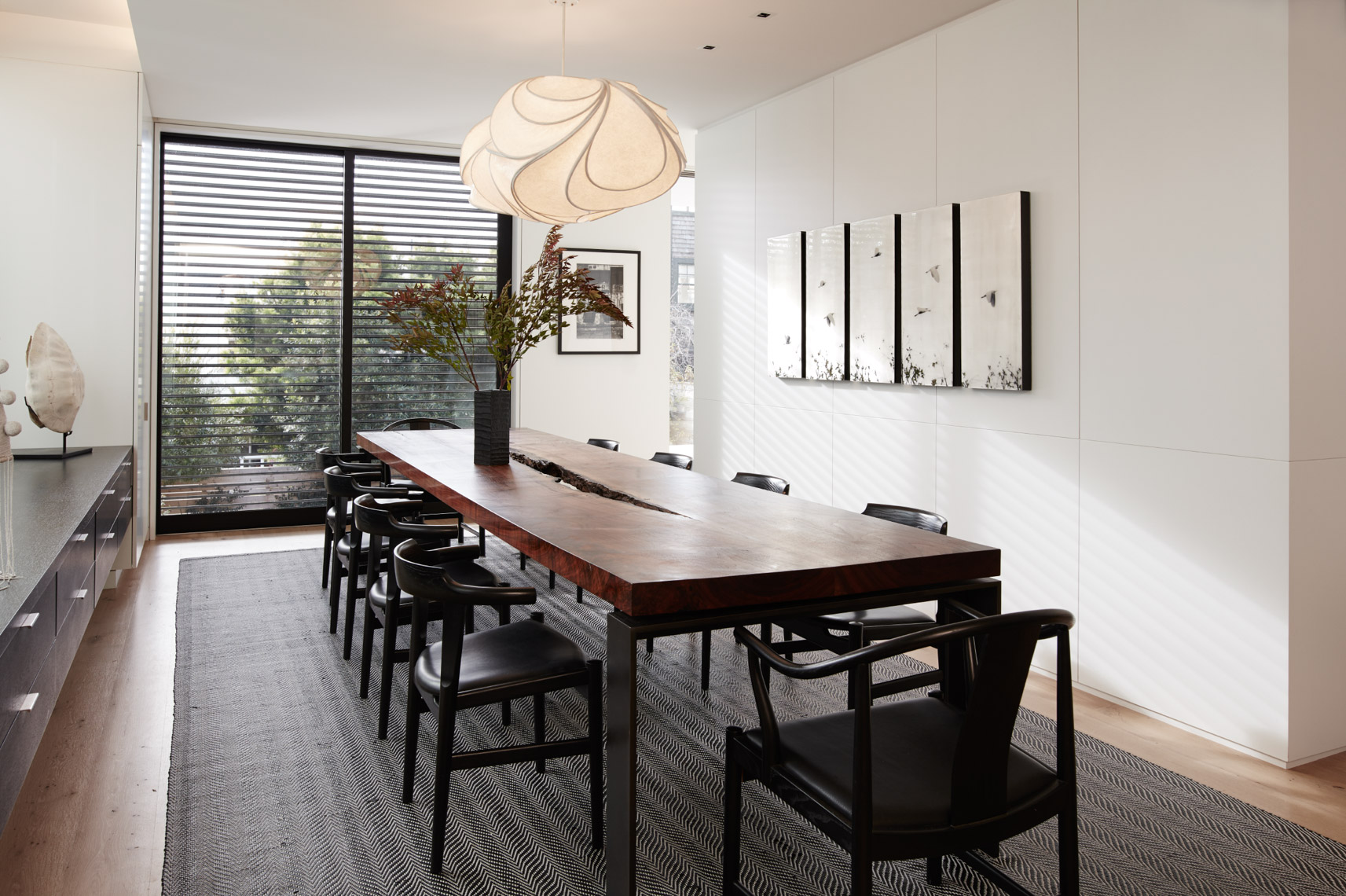 wooden dining room table with black chairs and ceiling lamp