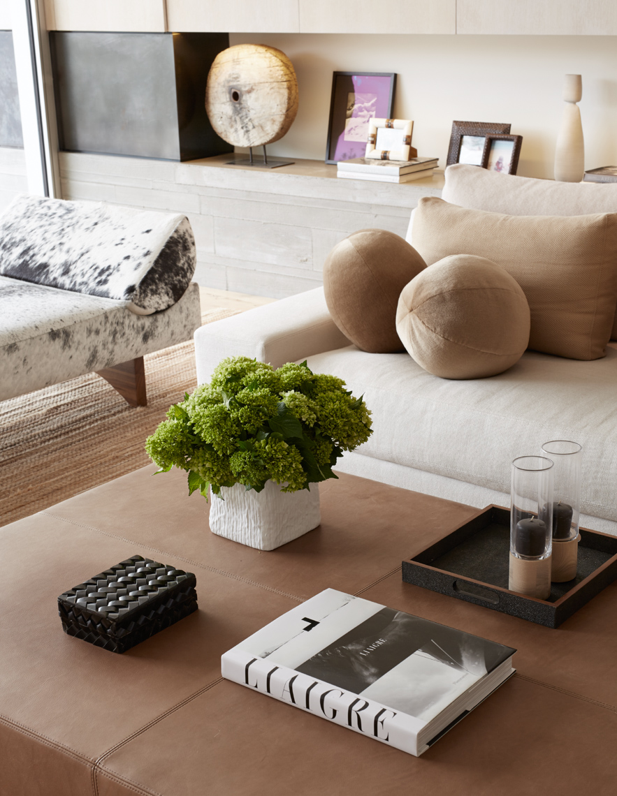 living room table with plant and book surrounded by beige seating