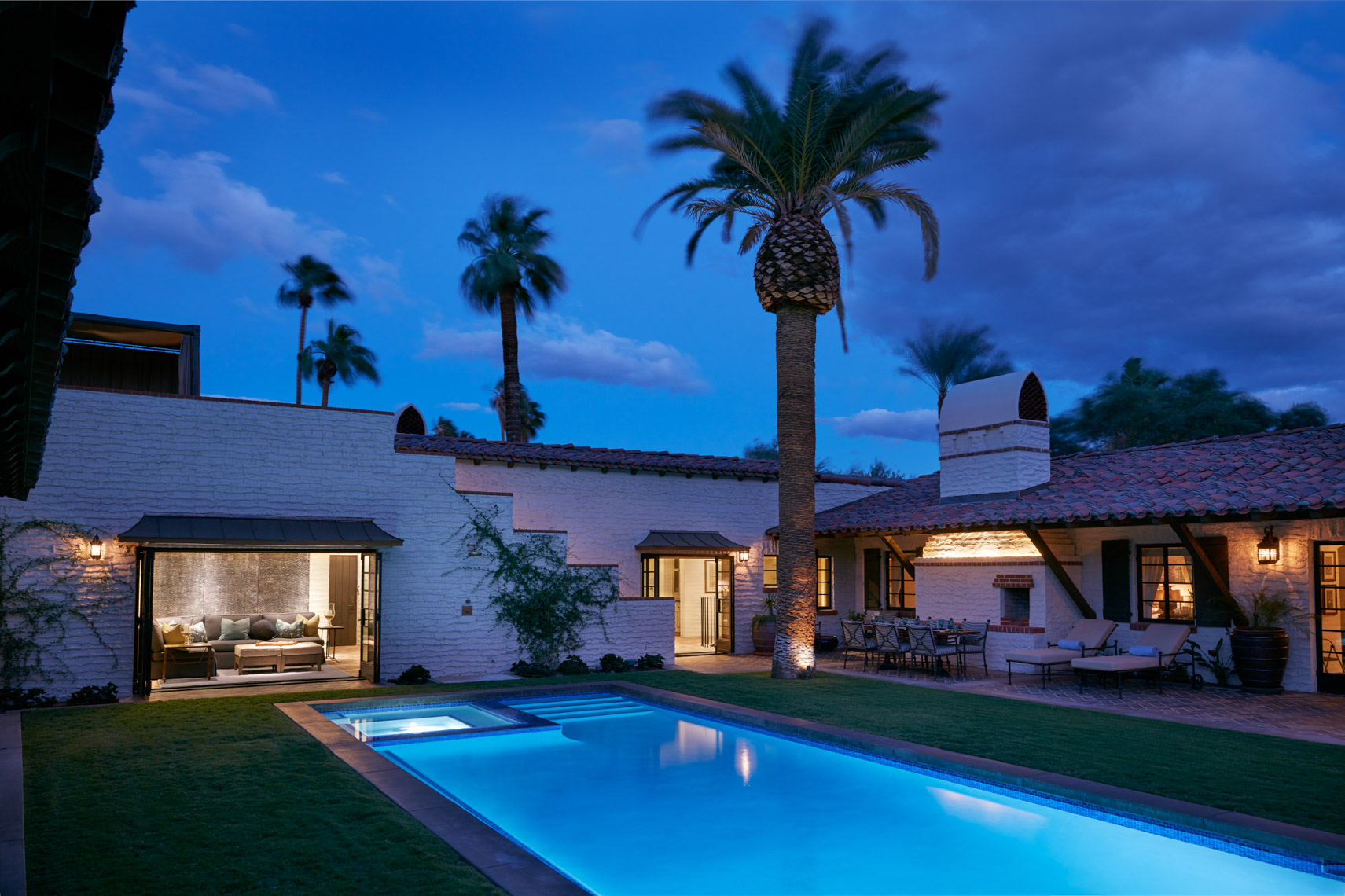 Blue pool at dusk with palm trees and courtyard