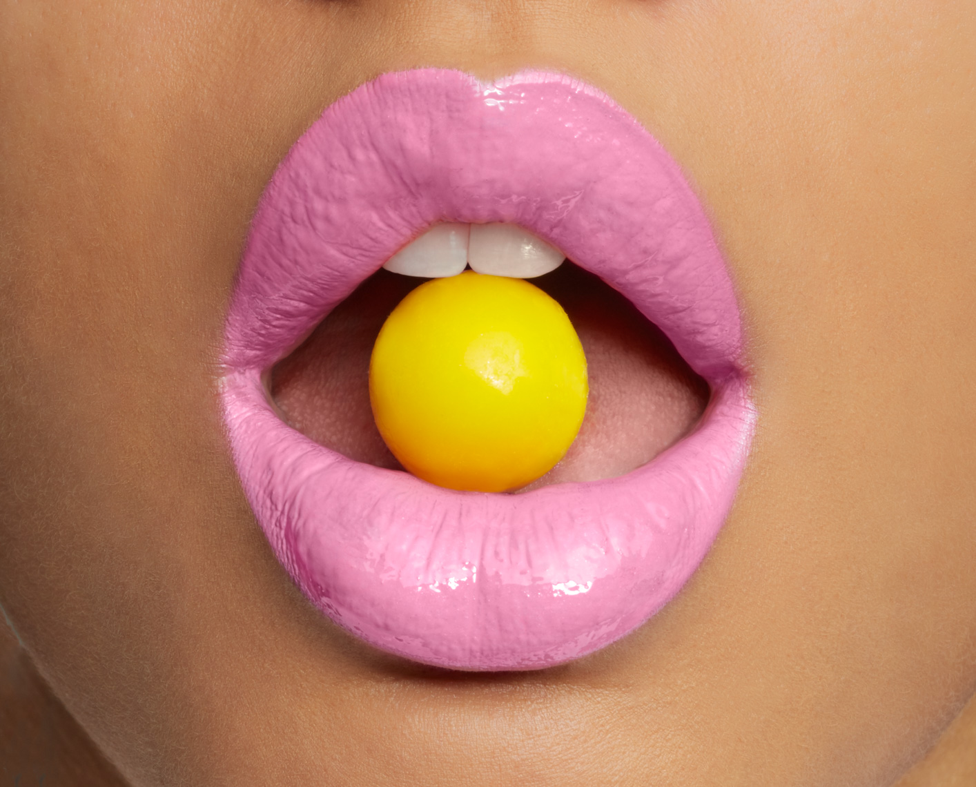 woman with pink lipstick and yellow candy between teeth