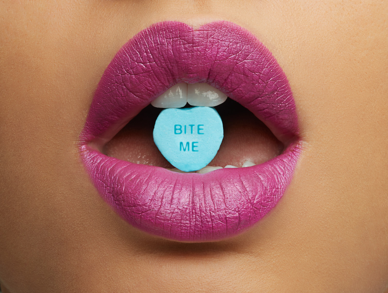 "woman with pink lipstick and blue valentine heart that says ""bite me"" San Francisco product photographer"