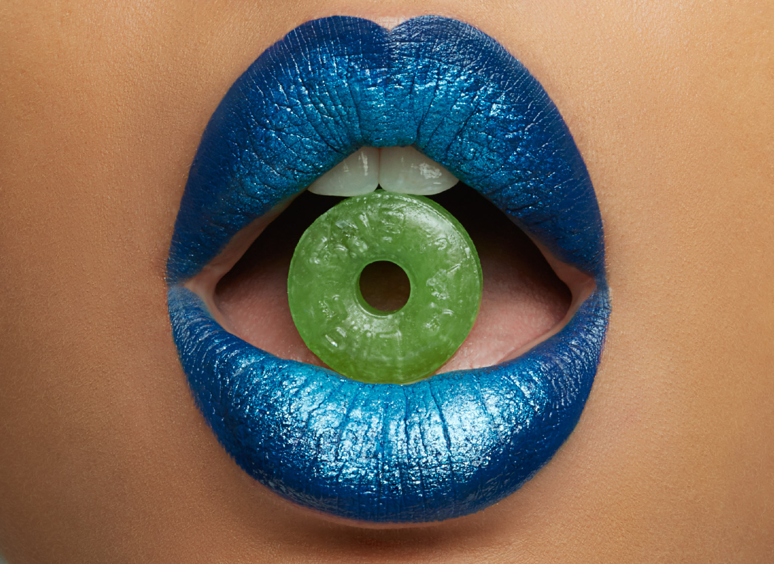 woman with blue shiny lipstick holding green candy between her teeth