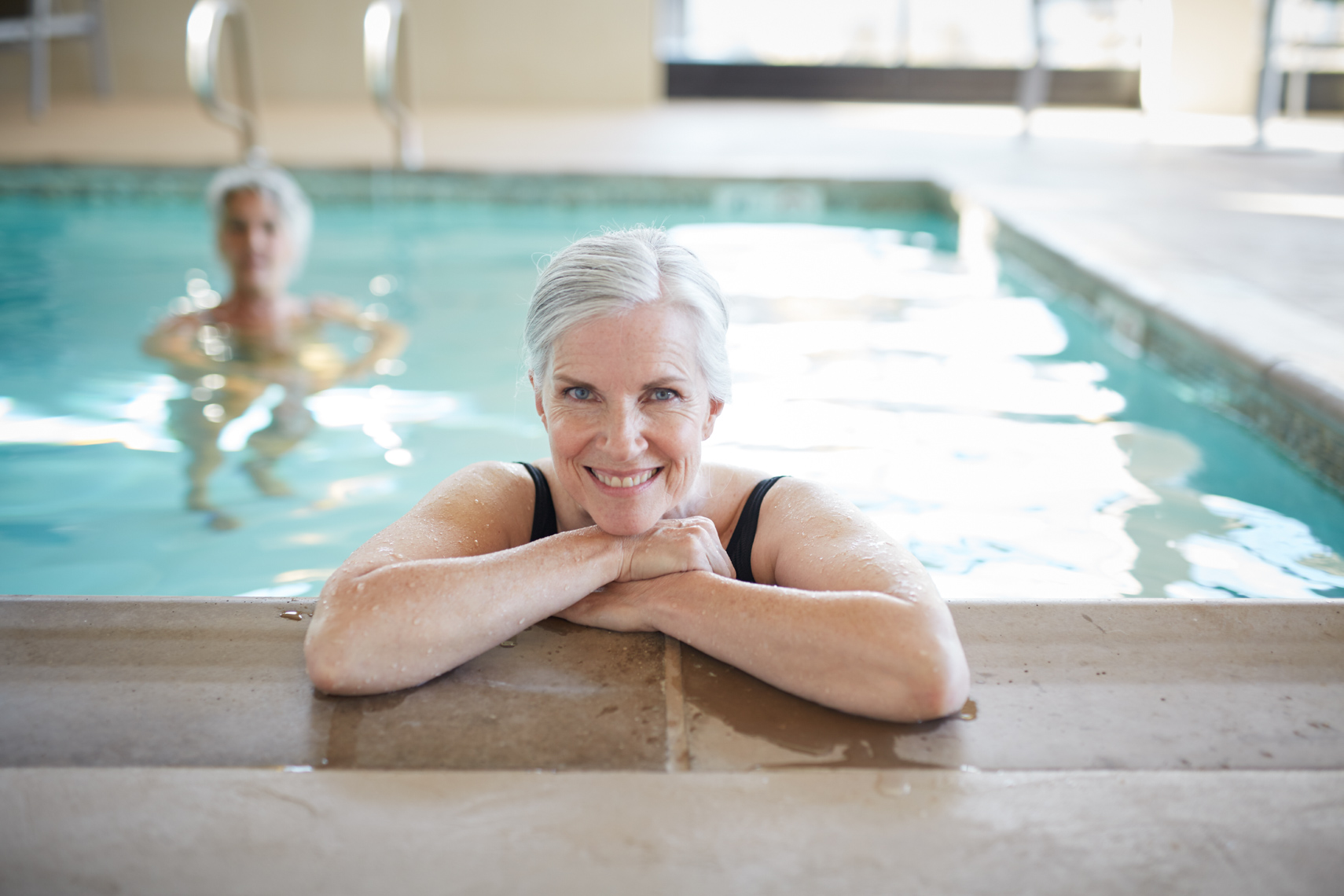 Elderly woman stands in an indoor pool looking at the camera her crossed arms over the pool combing