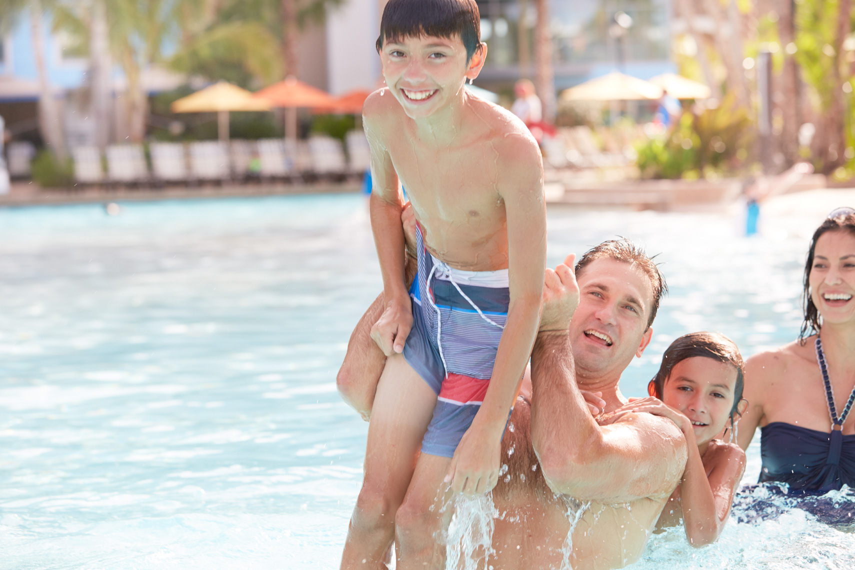 Dad playing with young boy in swimming pool with family near by on sunny day San Francisco lifestyle photographer