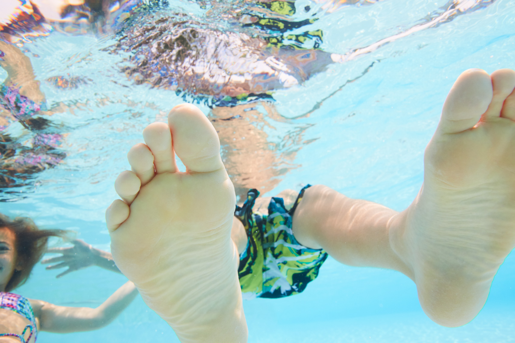 View of boys feet underwater looking up toward water surface