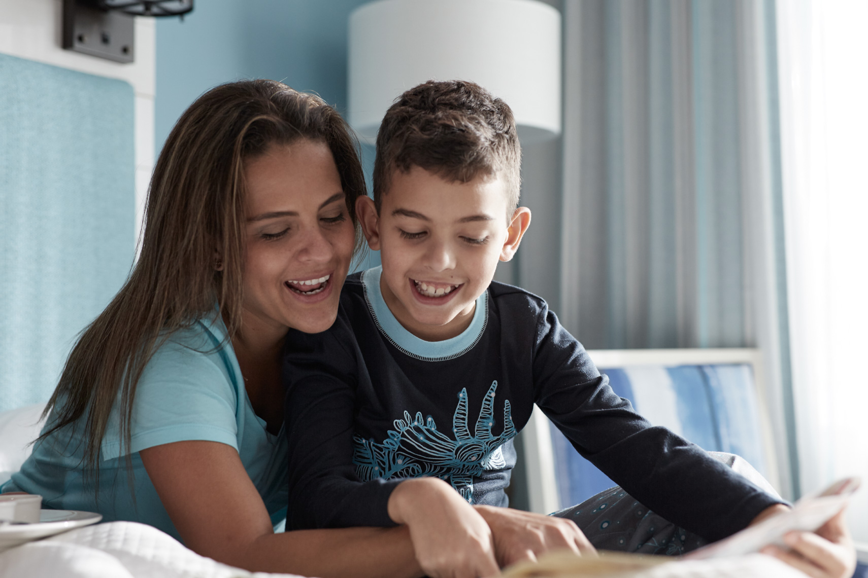 Mother and child laughing and looking at  a resort map in blue hotel room
