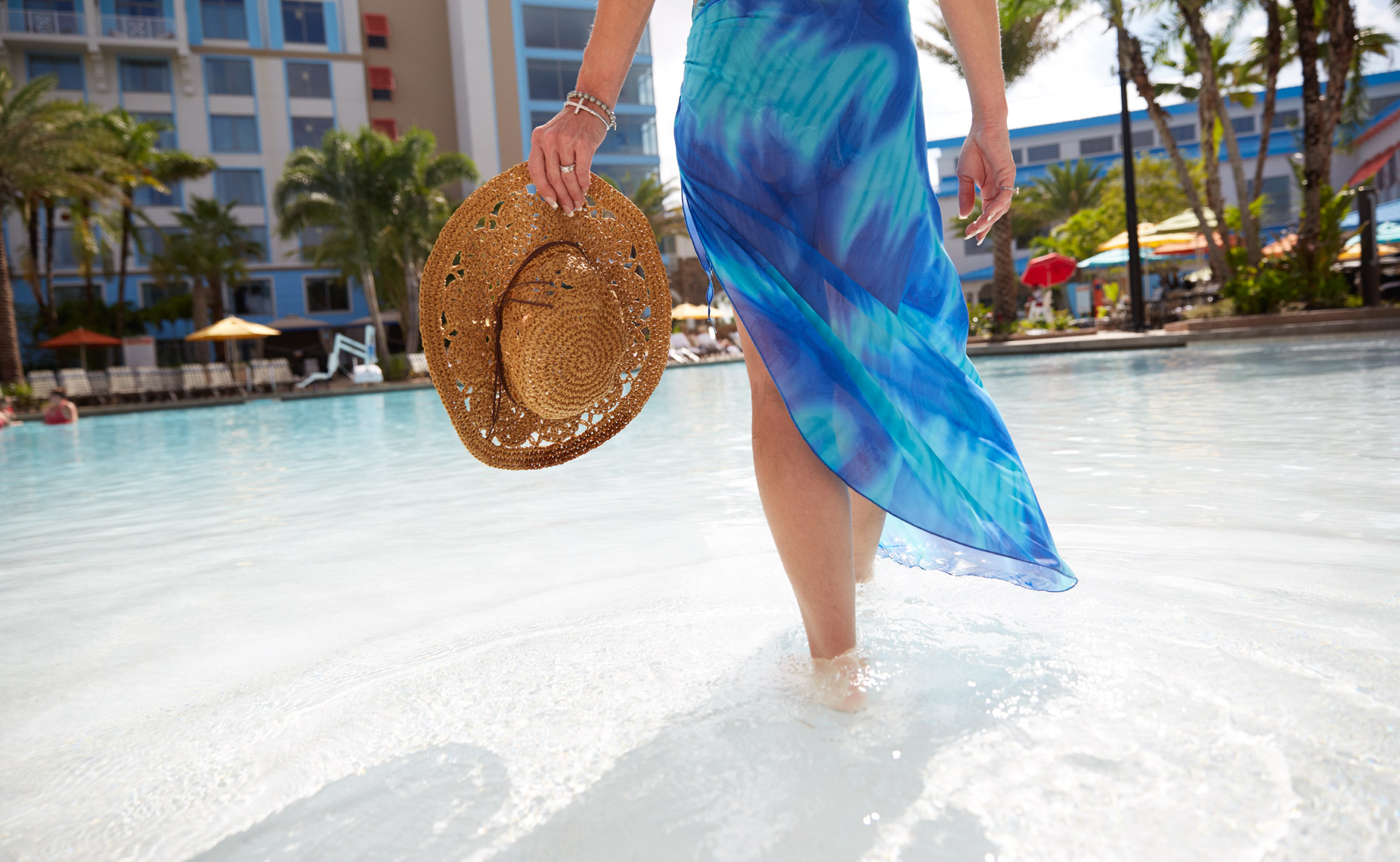 Woman in blue sarong walking in shallow pool carrying straw hat