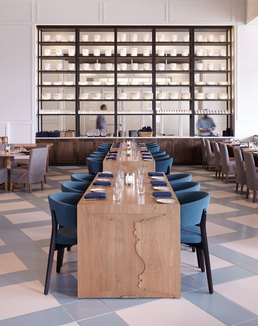 large dining area with wooden block tables and place settings and blue armchairs