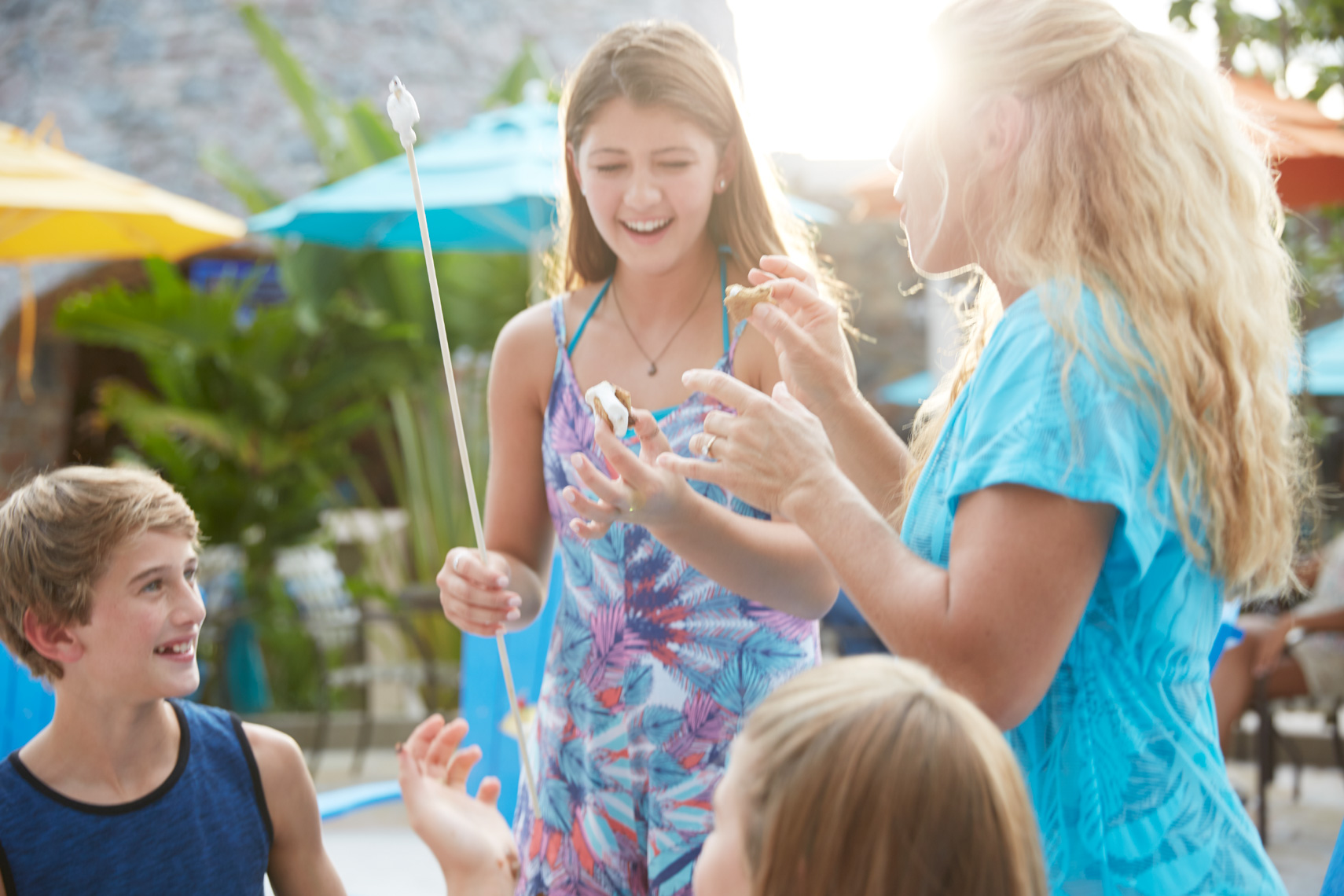 Family with mother and daughters and a son are laughing and roasting marshmallows in the afternoon surrounded by beach umbrellas
