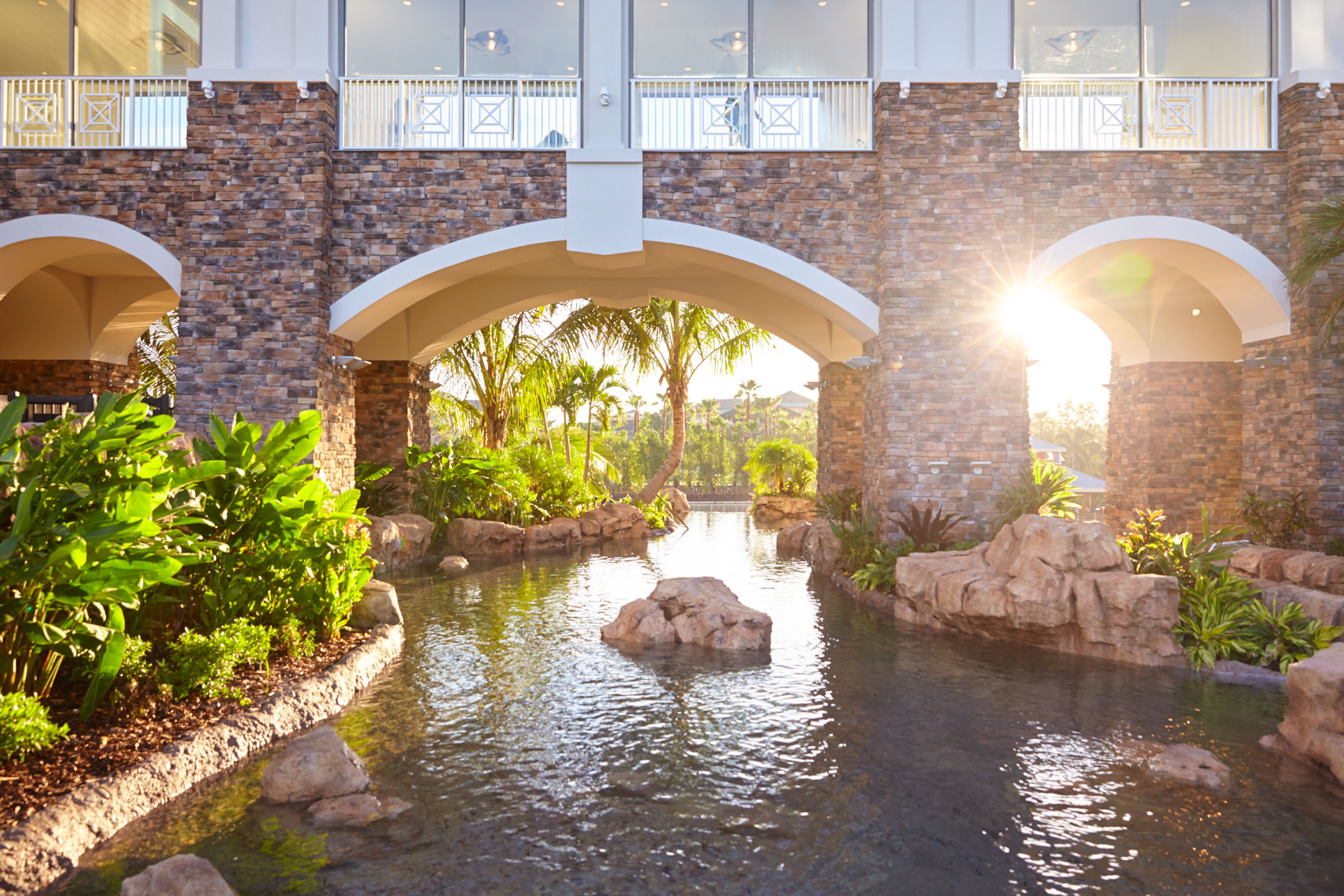 Tropical resort lagoon with bridge and arches at sunset
