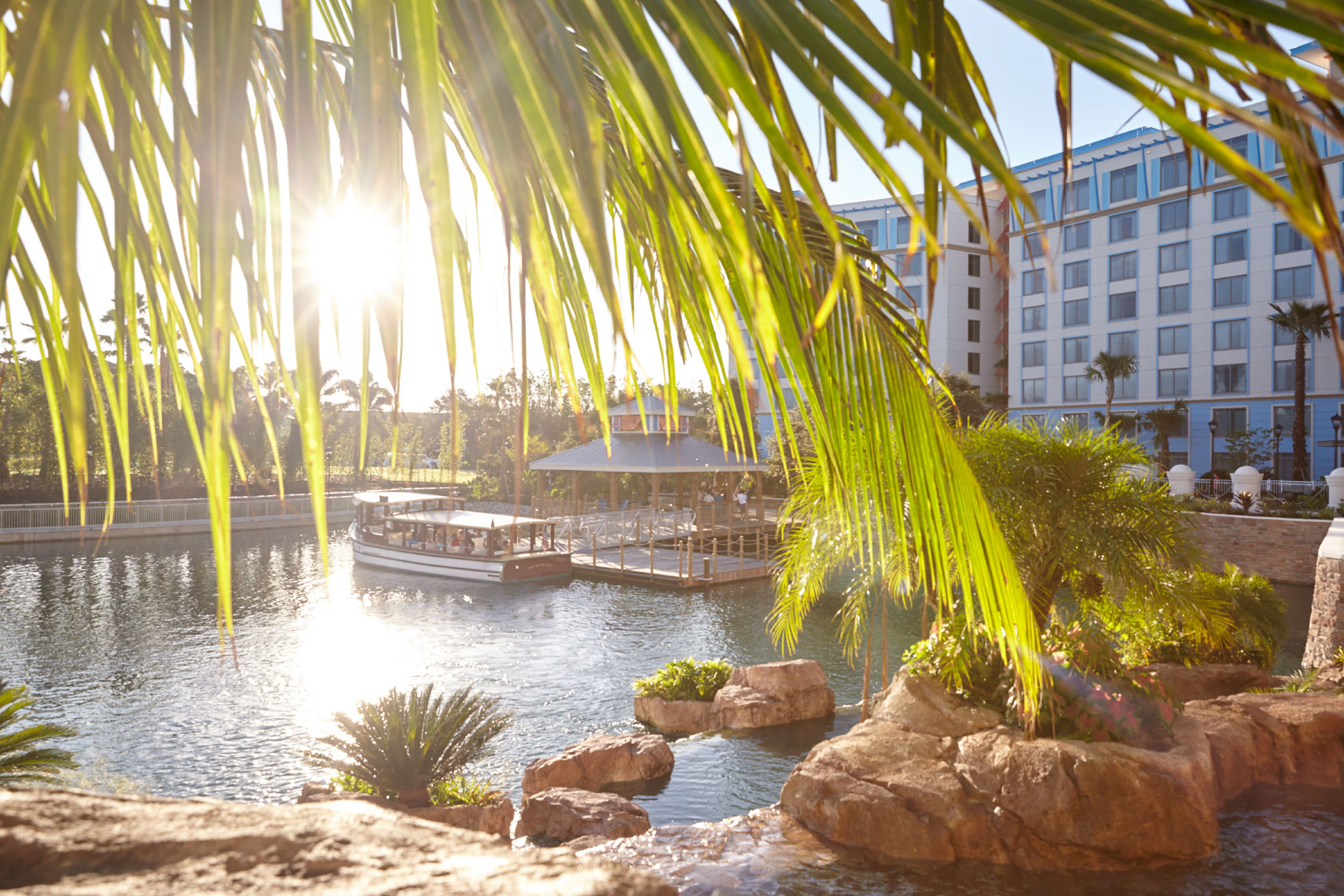 Tropical palm tree fronds framing lagoon with ferry and rocks at resort San Francisco interior photographer