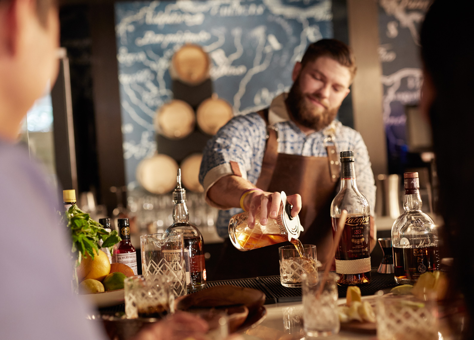 Male Bartender wearing brown apron preparing cocktails behind the bar