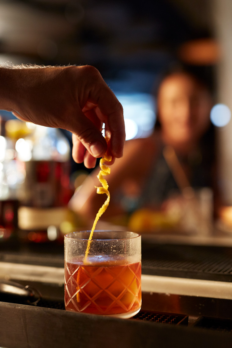 close up bar seen with man twisting lemon in drink San Francisco food photographer