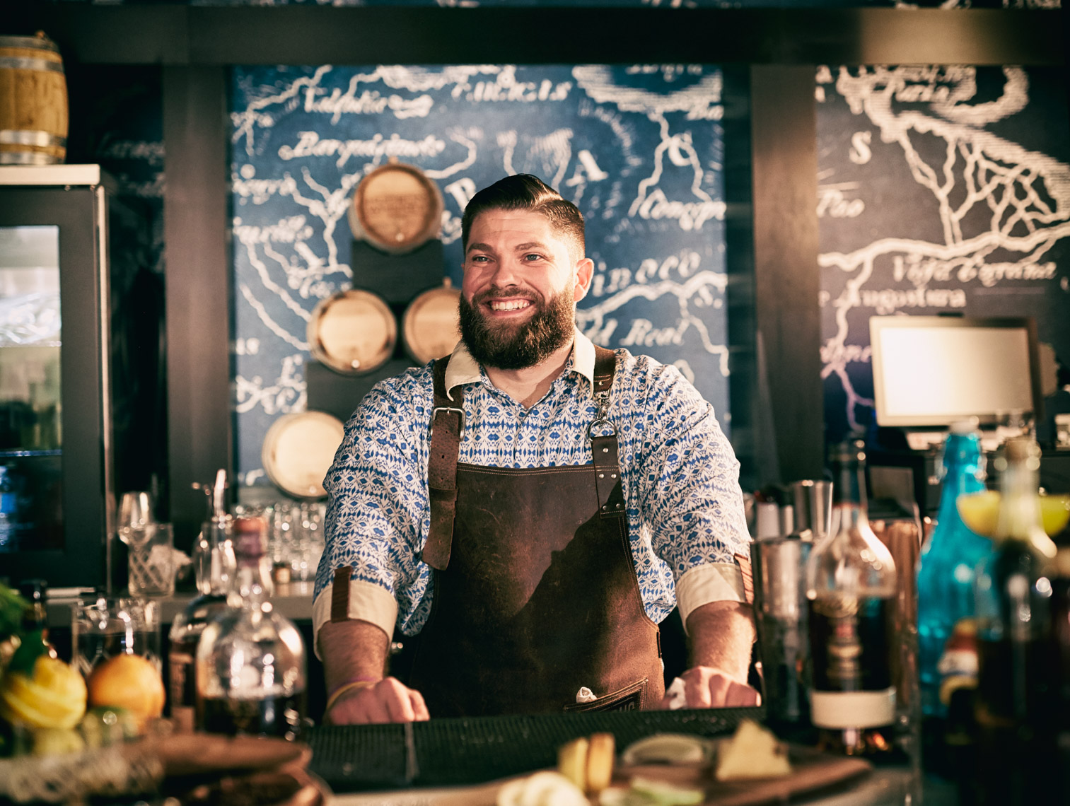 Bearded Male bartender in apron behind bar smiling