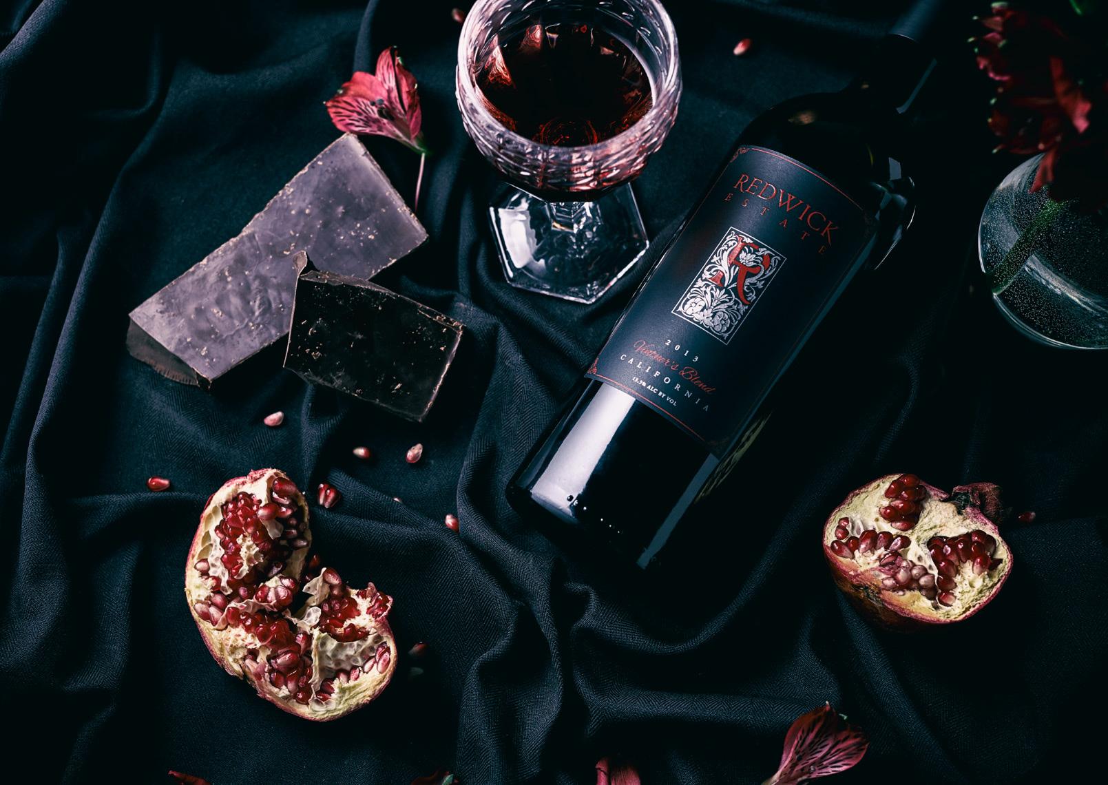 bottle and glass of wine with pomegranates and chocolate