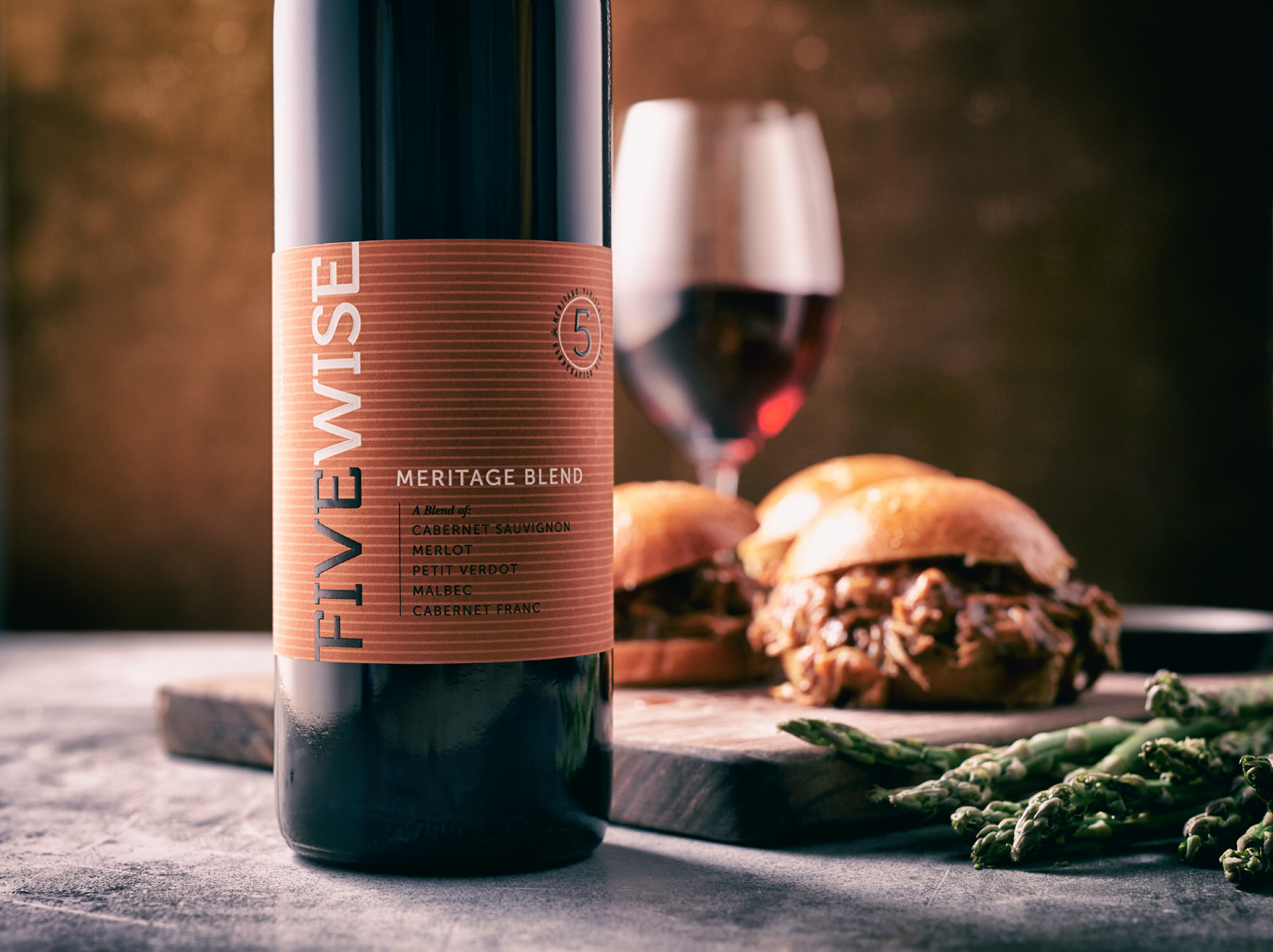 bottle and glass of wine with asparagus and sloppy joe burgers