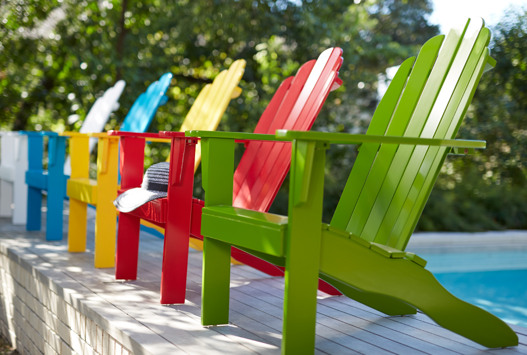 Colorful adirondack chairs in a row near pool