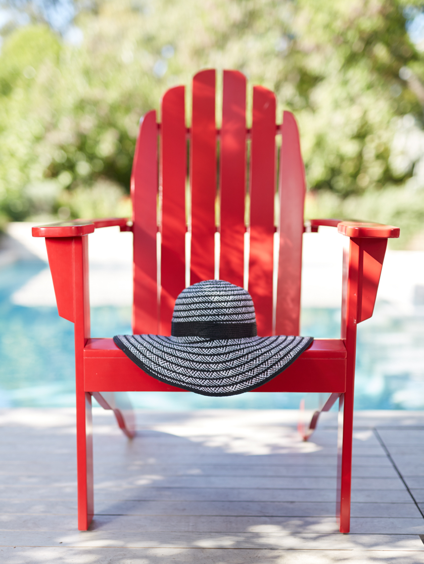 Red Adirondack chair straight on with straw hat outside