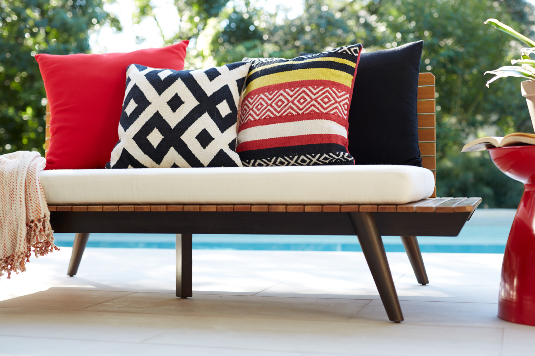 chic poolside bench with white cushion and 4 patterned pillows