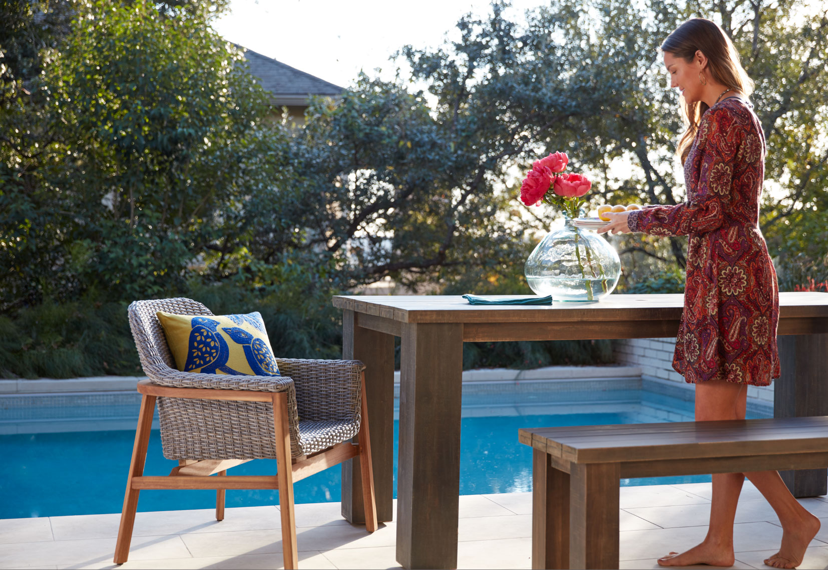 Woman in dress stands arranging flowers in a glass vase on a wooden table in the sun by the pool San Francisco lifestyle photographer