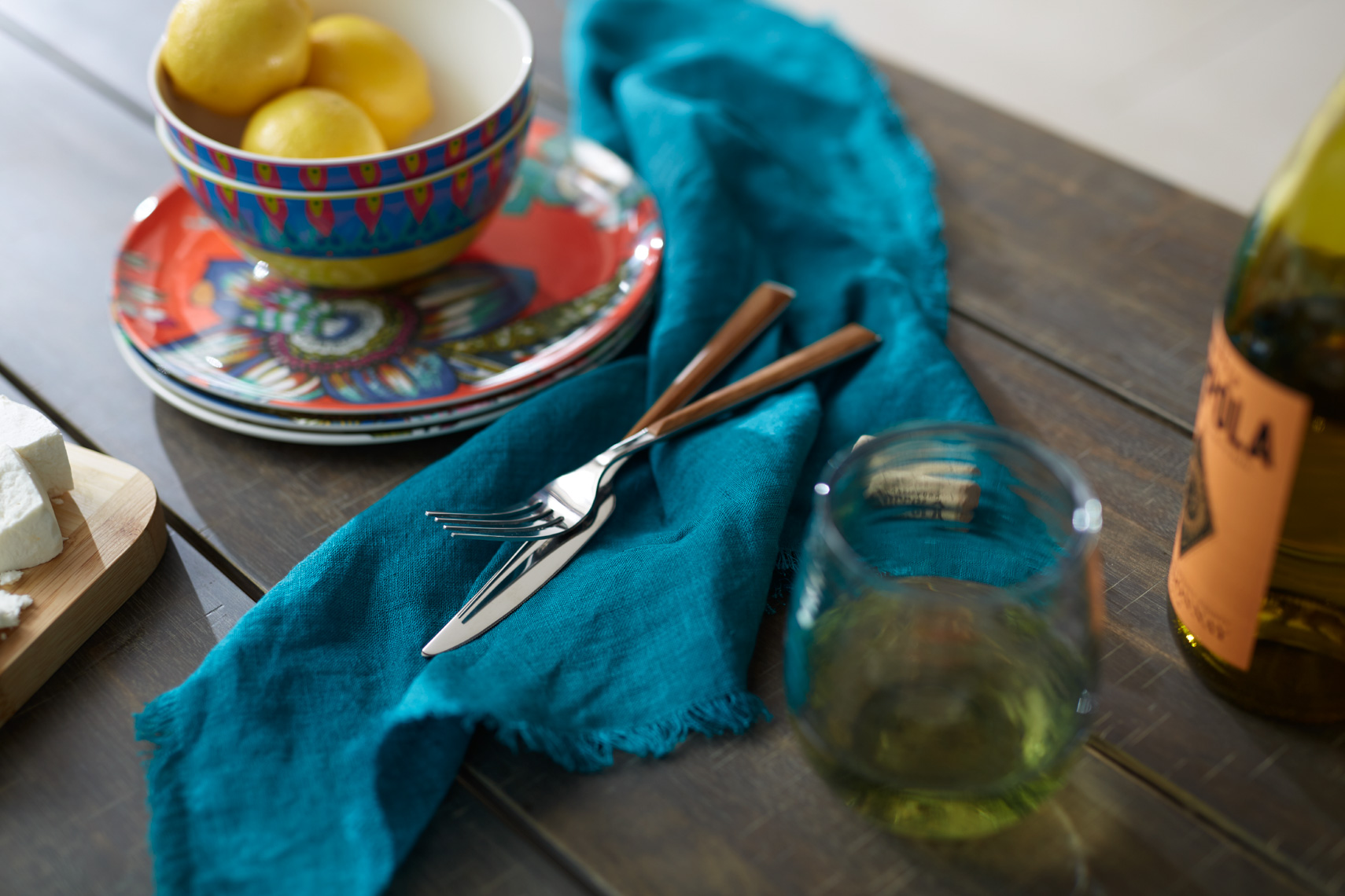 decorative plates and bowl with lemons and blue hand towel with silverware