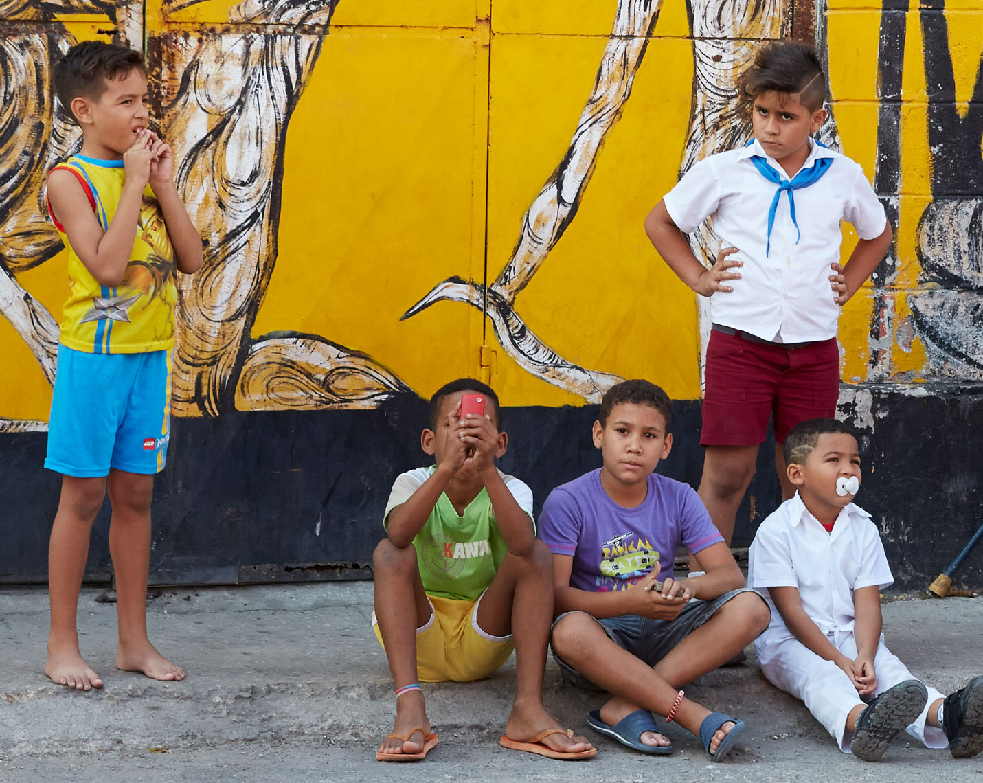 5 young boys with graphic design wall and colorful shirts in Cuba