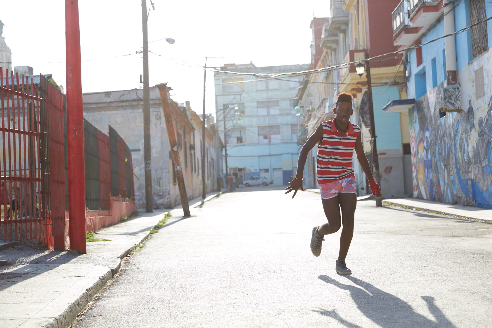 young boy running down the colorful empty street of Cuba