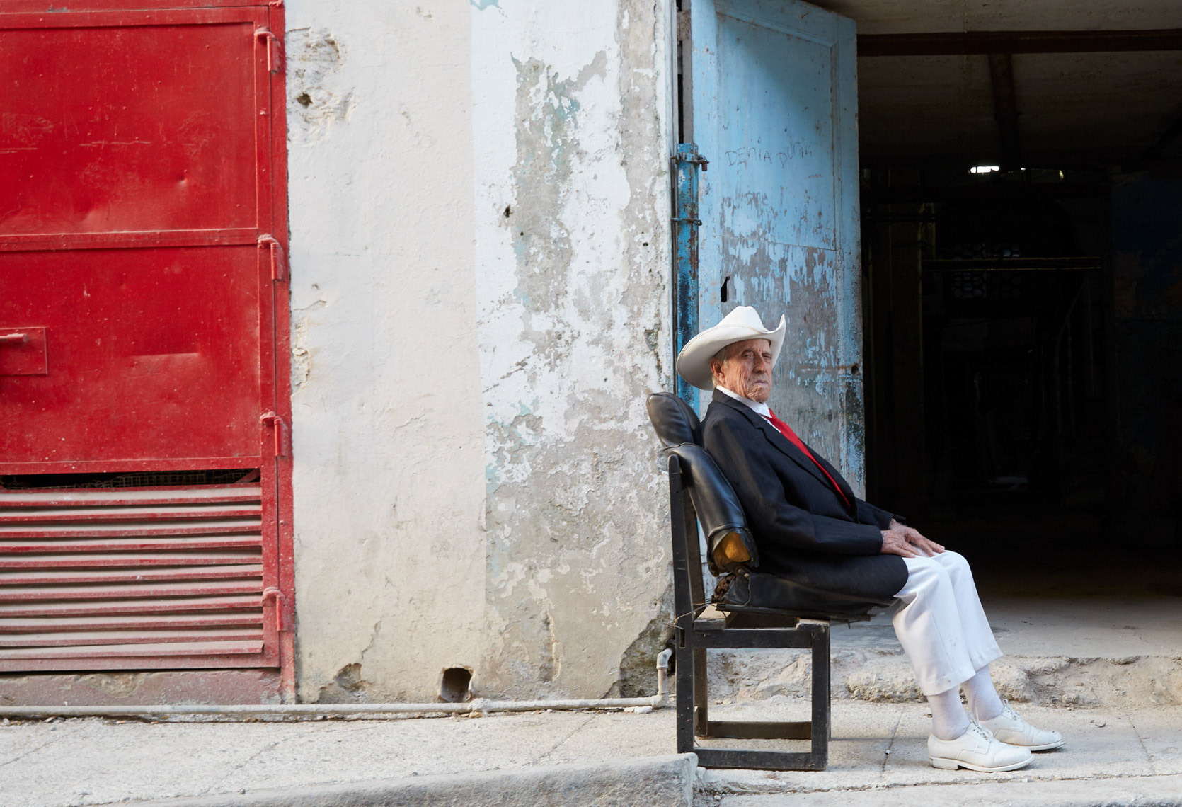 Cuban man sitting in old torn chair on sidewalk next to building with red white and blue walls