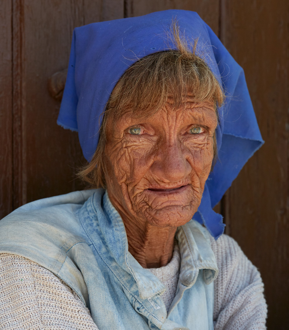 old woman with blue headband sitting against old wooden door