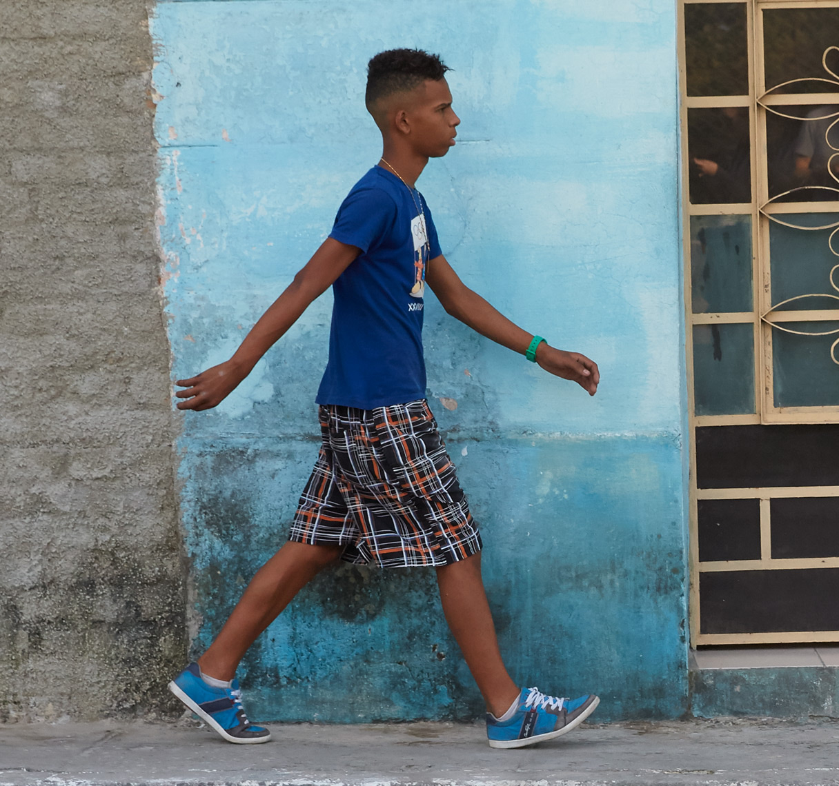 young boy in blue shirt walking in front of blue wall in cuba