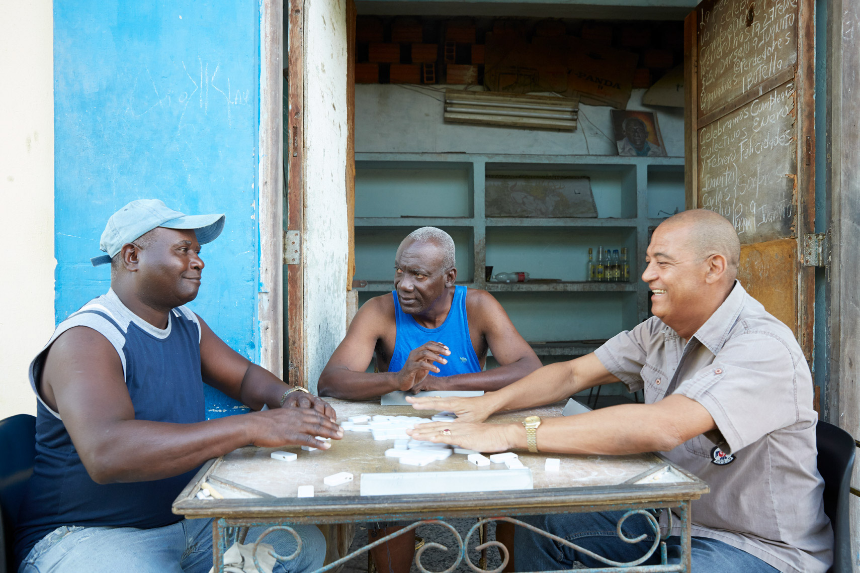 3 men playing dominos outside antique room in Cuba