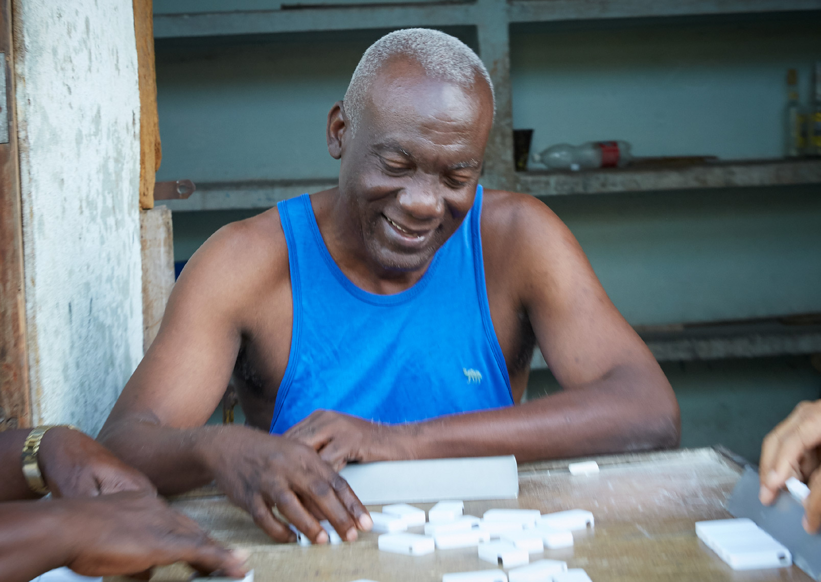 old man in blue shirt playing dominos in Cuba