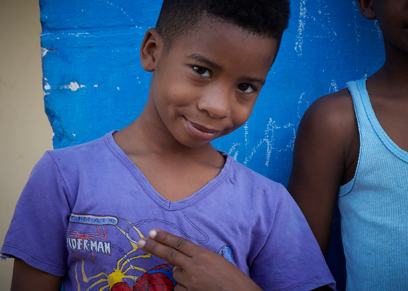 young boy with purple shirt and blue wall looking into camera holding up peace sign