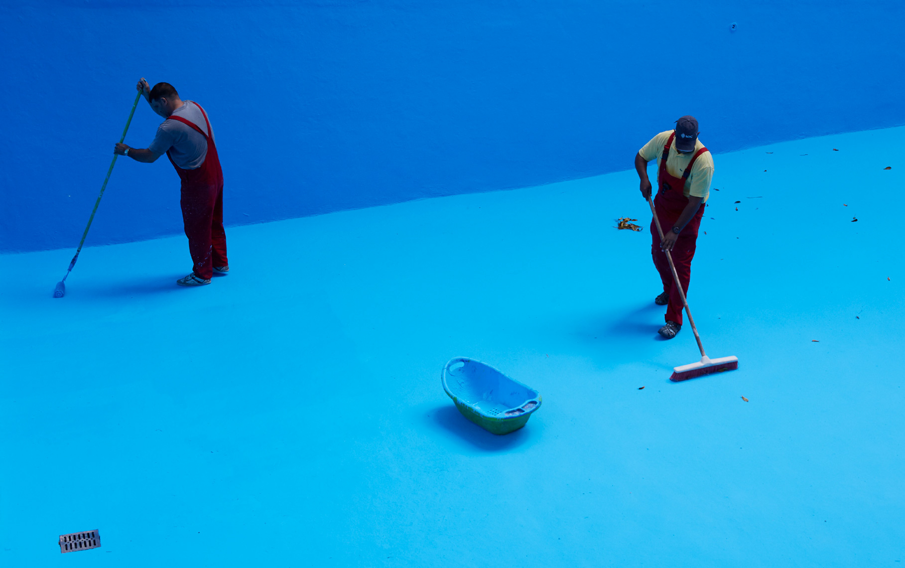 workers in red overalls painting large pool bright blue