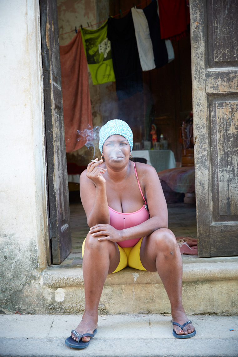 woman sitting on steps smoking cigarette in front of old house in Cuba